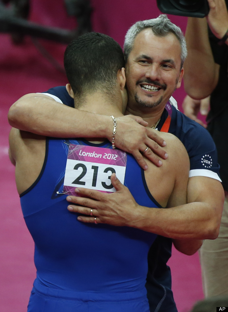 Stepfather and coach Yin Alvarez, right, hugs U.S. gymnast Danell Leyva after he won the bronze medal during the artistic gym
