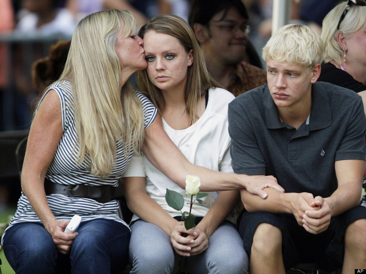 Family members of the victims of Friday's mass shooting in Aurora, Colo., comfort each other, Sunday, July 22, 2012, in Auror