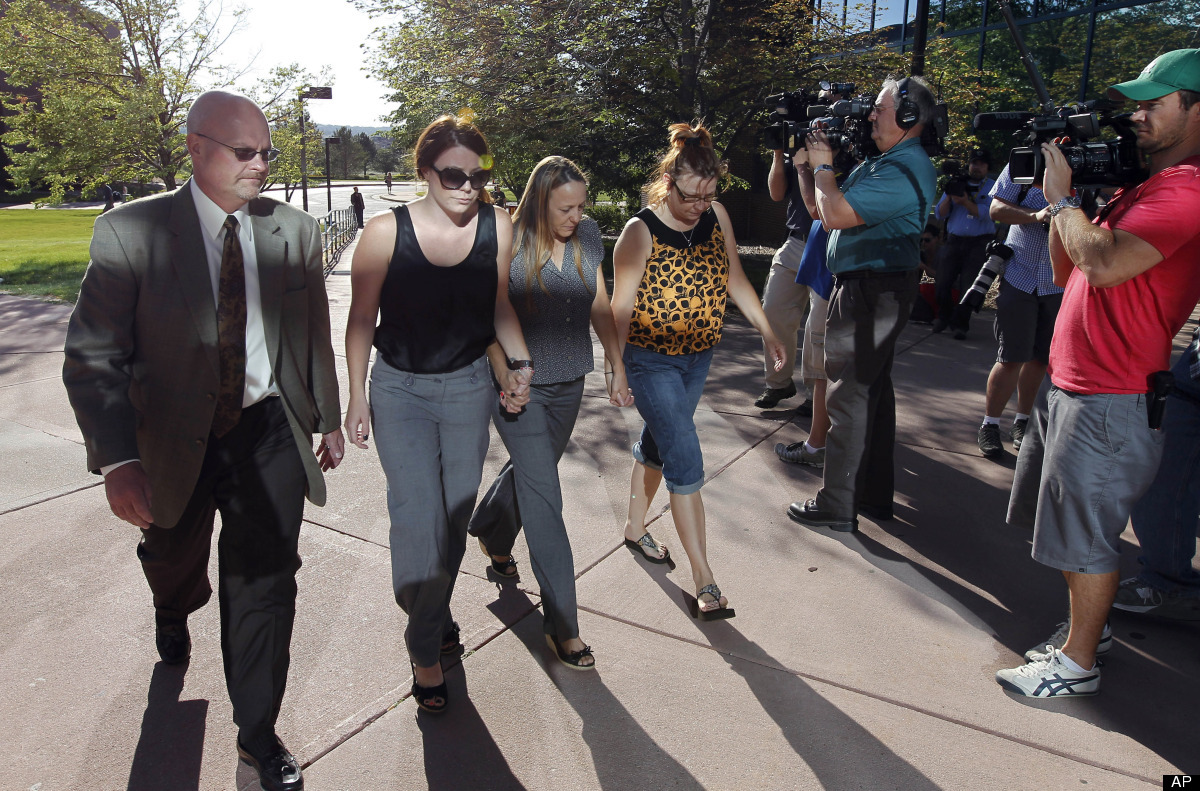 Family members of a victim from last week's theater shooting in Aurora, Colo., link hands as they arrive for a court appearan