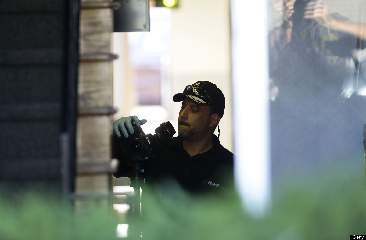 AURORA, CO - JULY 24:  A Federal Bureau of Investigation agent takes photos as he investigates inside the apartment building