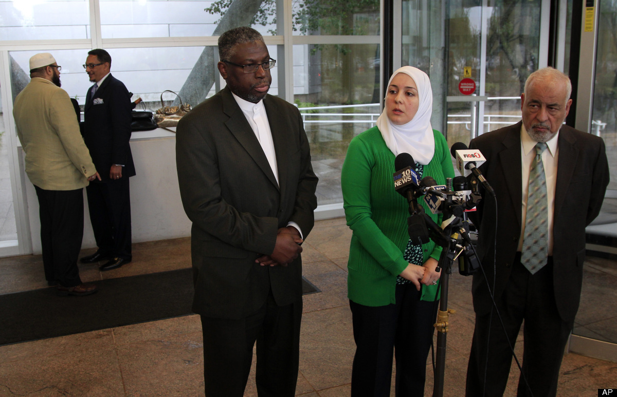 Imam Mustafa El-Amin, center, answers a question as he stands with Nadia Kahf, second right, attorney with the Council on Ame