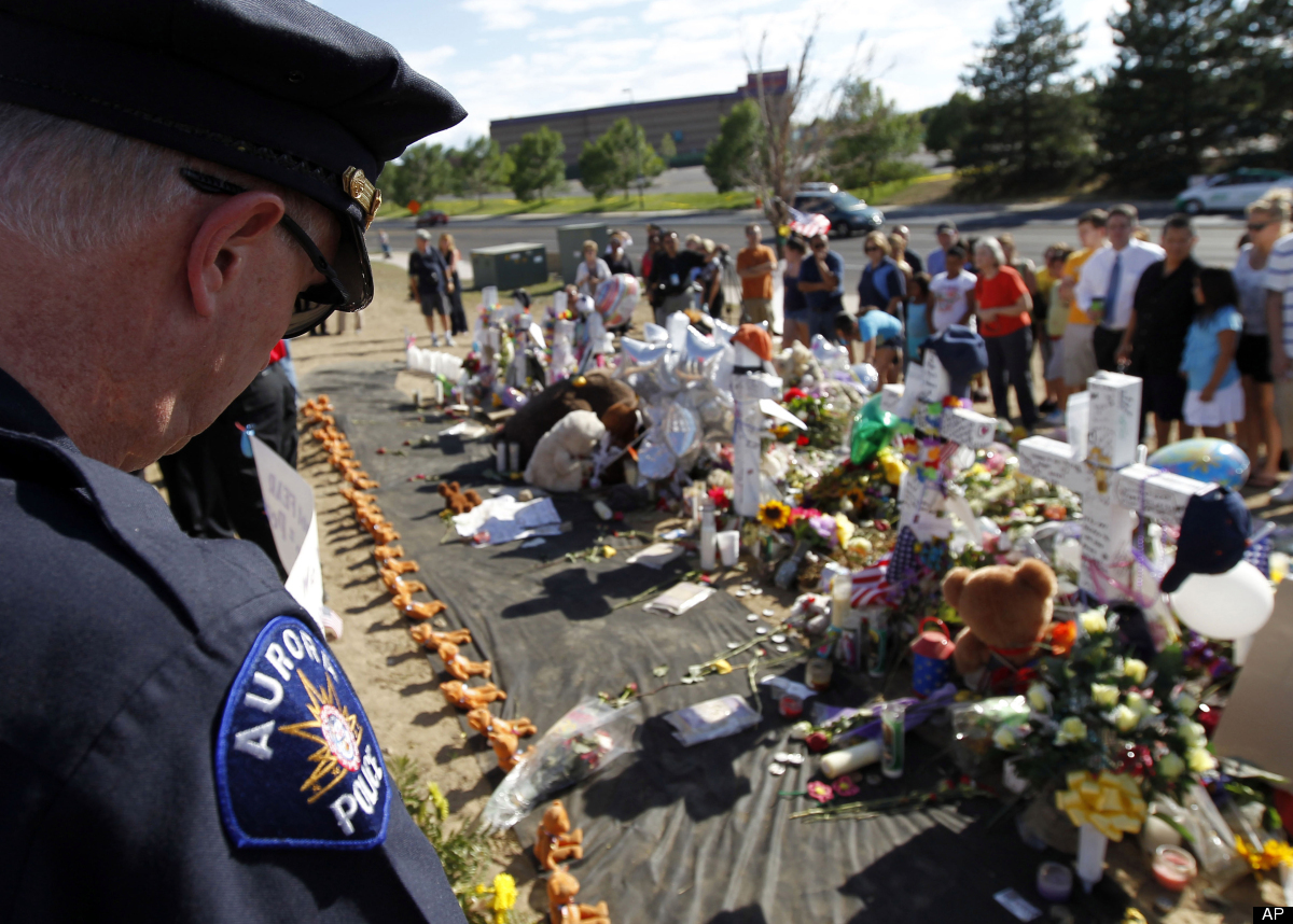 An Aurora police officer looks at the memorial across from the movie theater, Wednesday, July 25, 2012 in Aurora, Colo. Twelv