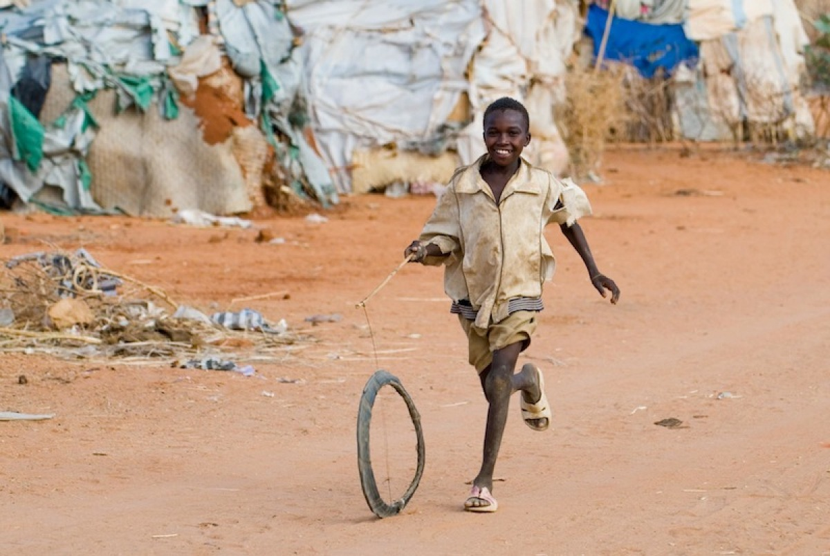 In the Dereig refugee camp in Darfur, this little boy has found a way to have fun using a homemade hoop.