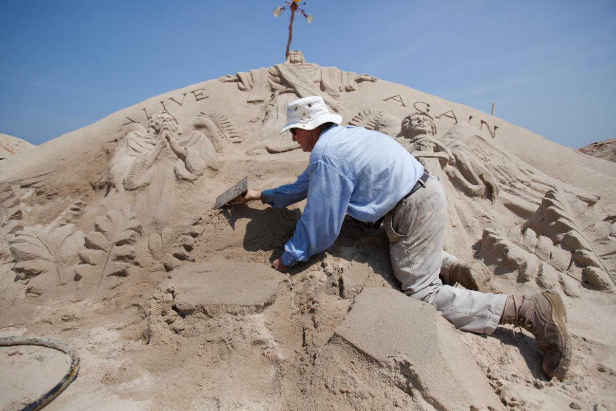 Artist Randy Hofman repairs one of his existing sand sculptures on the beach in Ocean City, Md., on July 17, 2012. Hofman has
