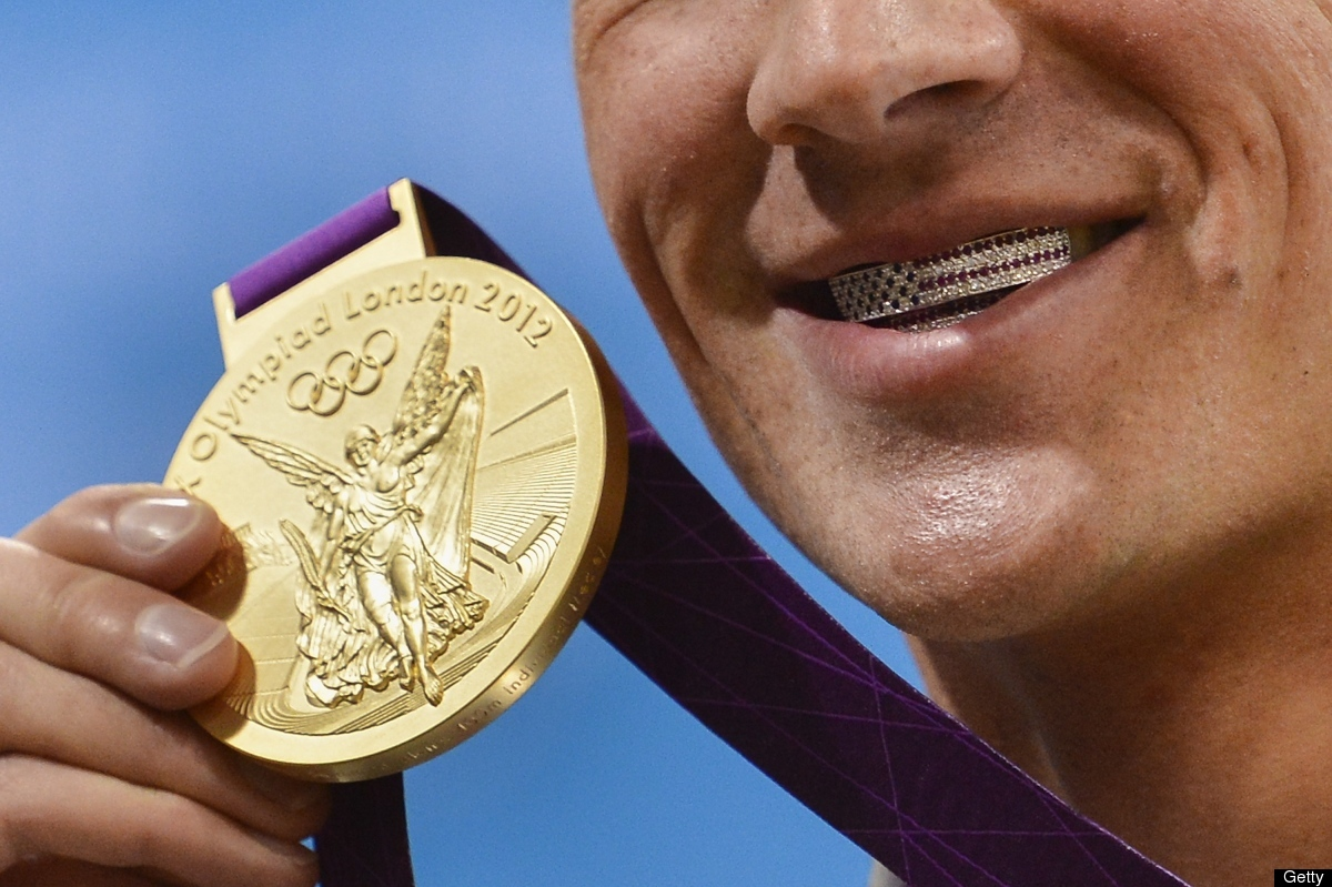 US swimmer Ryan Lochte poses with his dental braces bearing the US flag and his gold medal after winning the men's 400m indiv