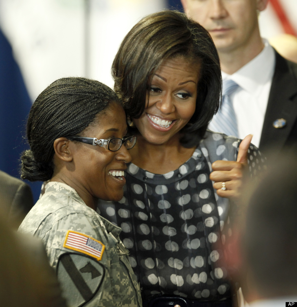 First lady Michelle Obama poses with a member of the military after Illinois Gov. Pat Quinn signed into law a measure allowin