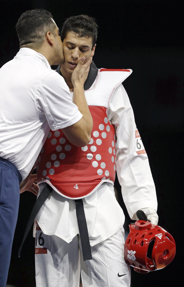 United States' Steven Lopez, right, gets a kiss from his coach Jean Lopez after losing to Azerbaijan's Ramin Azizov in men's