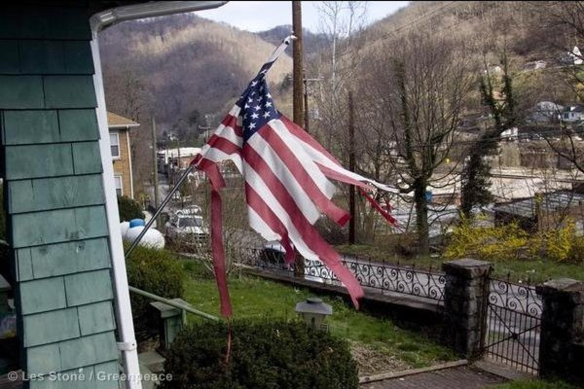 A tattered U.S. flag hangs from a house in the mining town of Norfolk. Health care is an unaffordable luxury in McDowell Coun