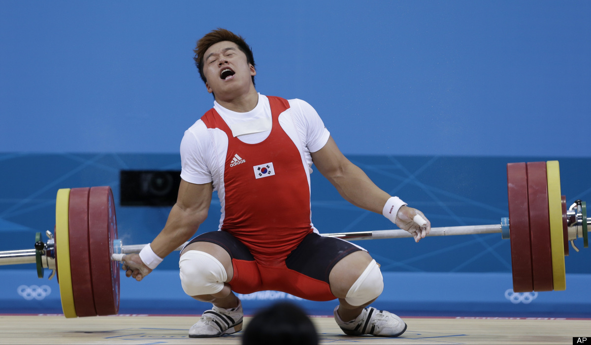 Sa Jae-hyouk of South Korea reacts after getting injured on a lift during the men's 77-kg weightlifting competition at the 20