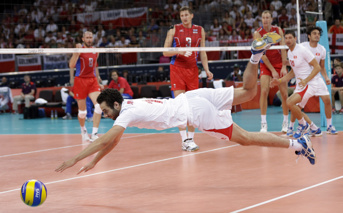 Tunisia's Ismail Moalla (11) dives for a spike by Russia during a men's volleyball preliminary match at the 2012 Summer Olymp