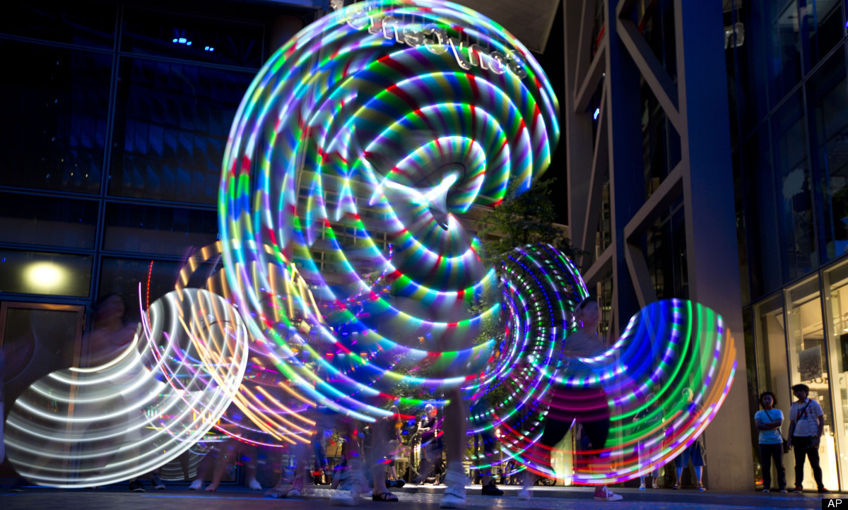 Hoopers perform with their illuminated hula hoops during a flash mob at Potsdam Square (Potsdamer Platz) in Berlin, Germany,