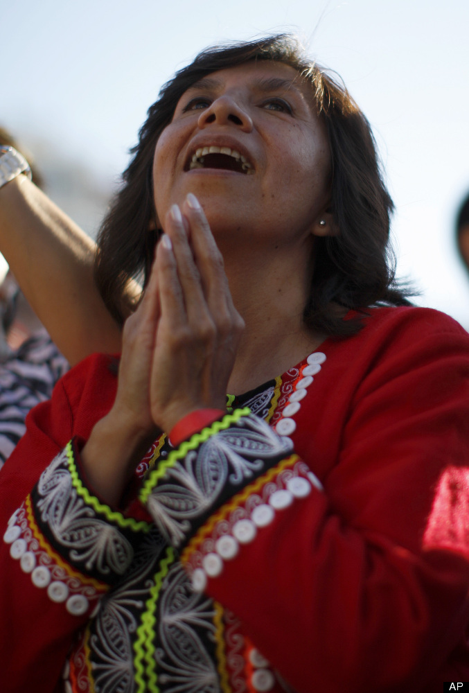 A woman sings as people pay homage to Our Lady of Guadalupe during an event in her honor at the Los Angeles Memorial Coliseum