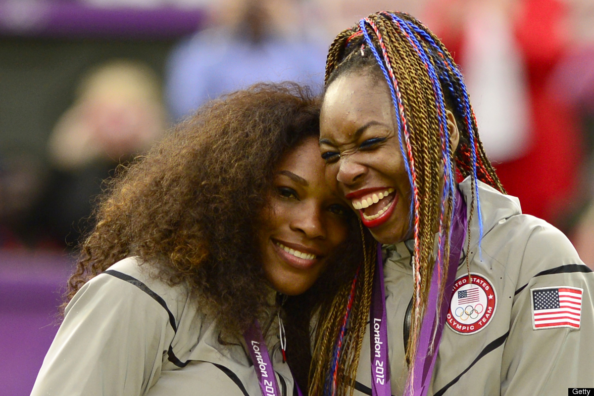 US Serena Williams (L) and Venus Williams celebrate on the podium after receiving their gold medal for winning the London 201