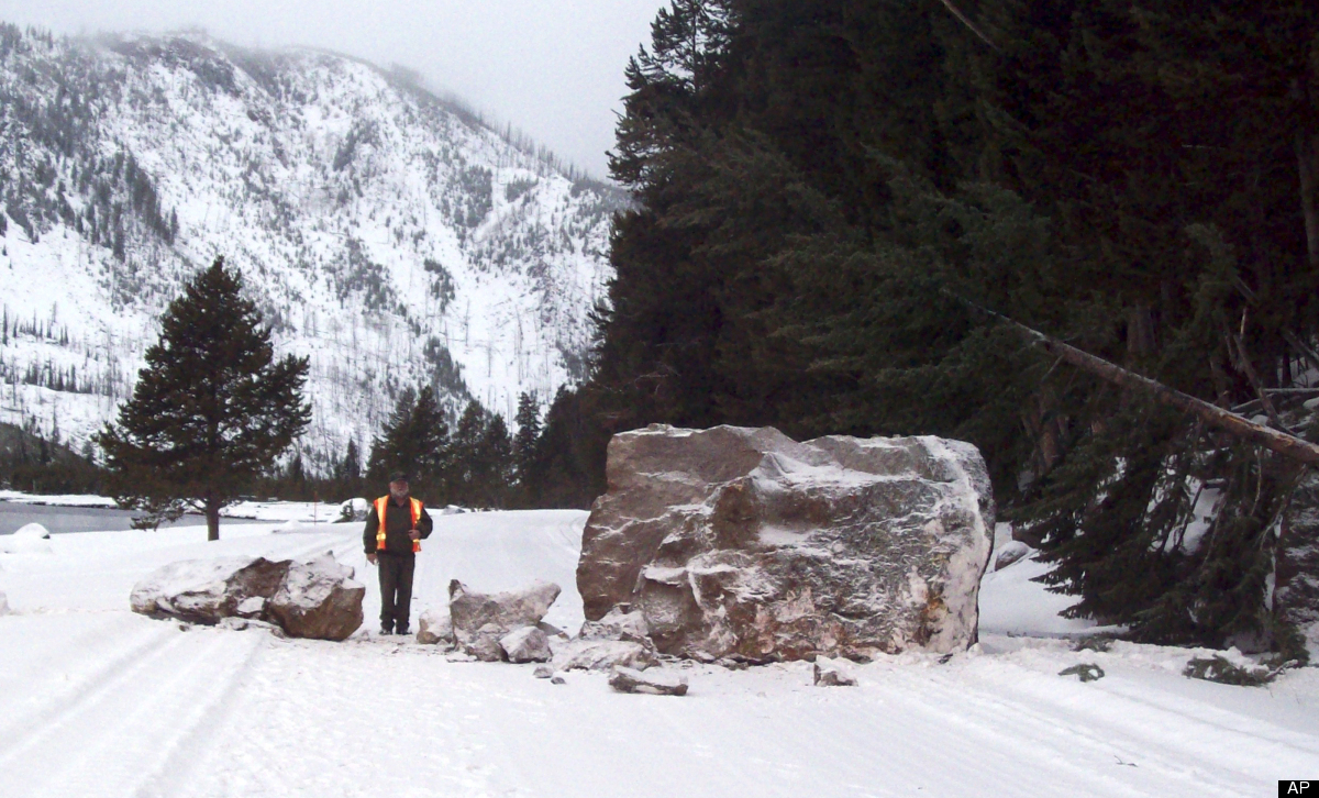 This photo provided by the National Park Service shows an unidentified man standing by an SUV-sized boulder sitting on Yellow