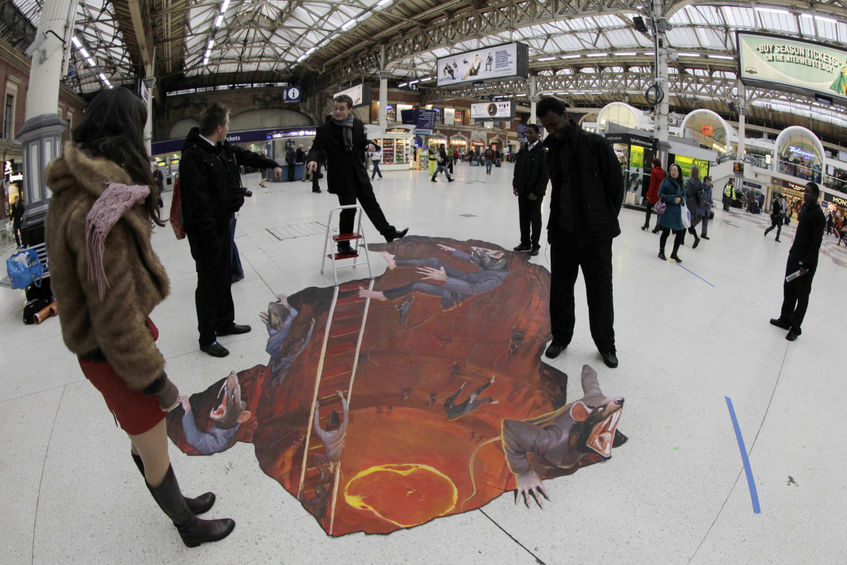 "Commuters step around a 3D art exhibit entitled ""Escape the Rat Race"" painted on the concourse of Victoria railway station in"