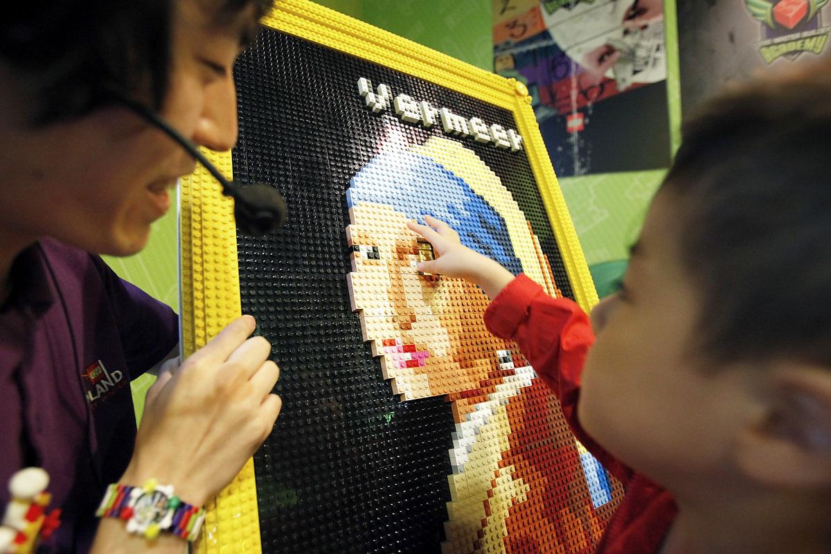 Lego master model builder Yoshihiro Osawa helps a boy attach a piece of Lego bricks to a replica of Johannes Vermeer's 'Girl