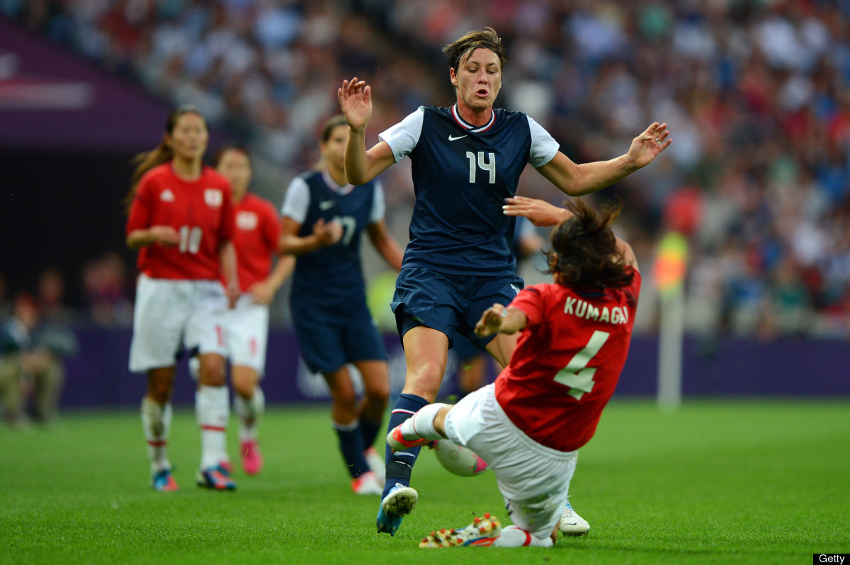 Abby Wambach #14 of United States gets tripped up by Saki Kumagai #4 of Japan during the Women's Football gold medal match on