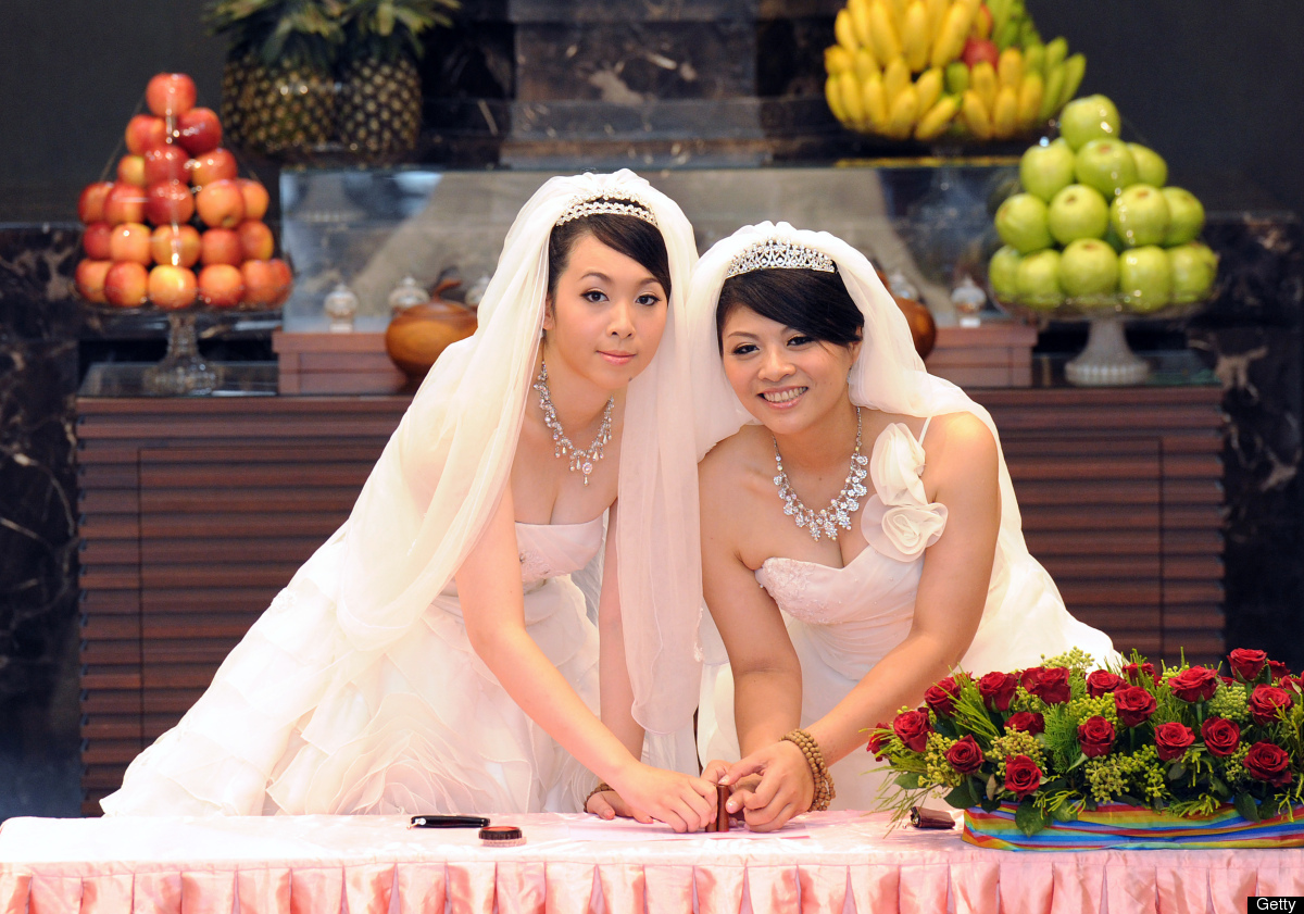 Taiwanese women Fish Huang (R) and her partner You Ya-ting cast their stamps during their same-sex Buddhist wedding ceremony