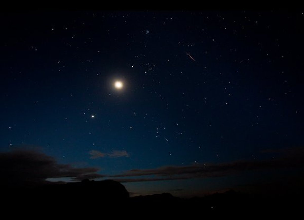 The moon and Venus shine bright alongside a Perseid meteor (upper right) on Aug. 12 in this view by photographer Tyler Leavit