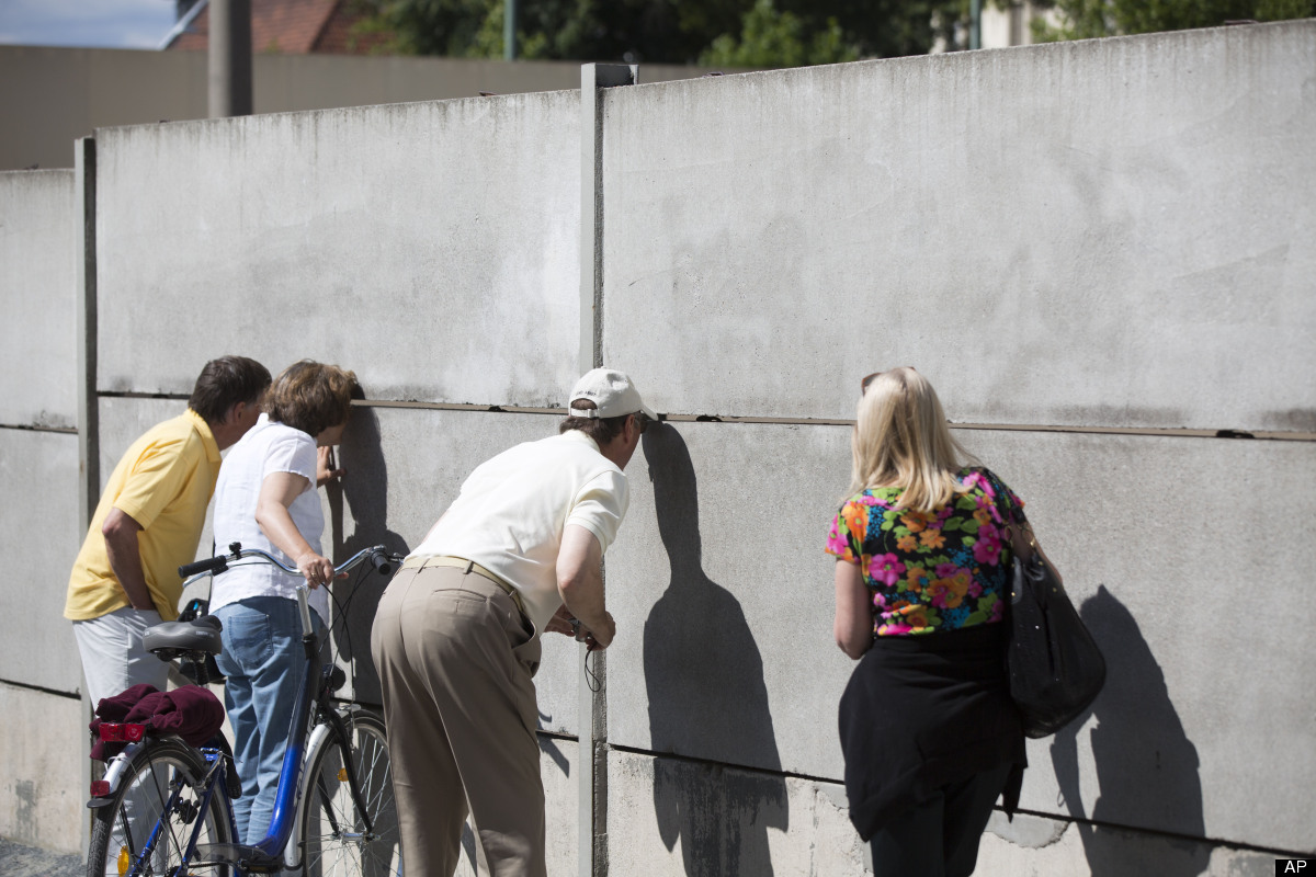 People look through a slot in a segment of the Berlin wall at the Berlin Wall Memorial at Bernauer Strasse in Berlin, Germany