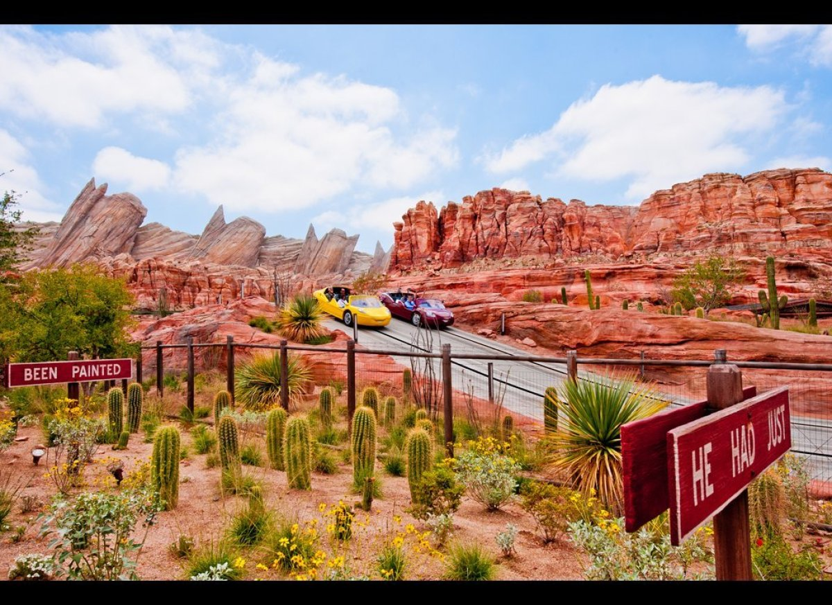 Two cars race through Ornament Valley on Radiator Springs Racers in Cars Land.