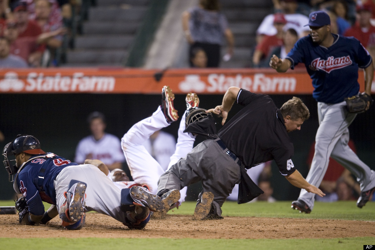 Home plate umpire Greb Gibson falls to the ground after inadvertently getting spiked in the face by the Angels Torii Hunter a