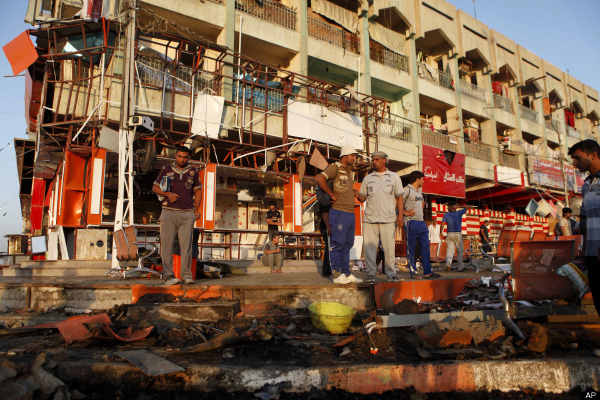 People inspect the aftermath of an overnight car bomb attack in Baghdad's Shiite enclave of Sadr City, Iraq, Friday, Aug. 17,