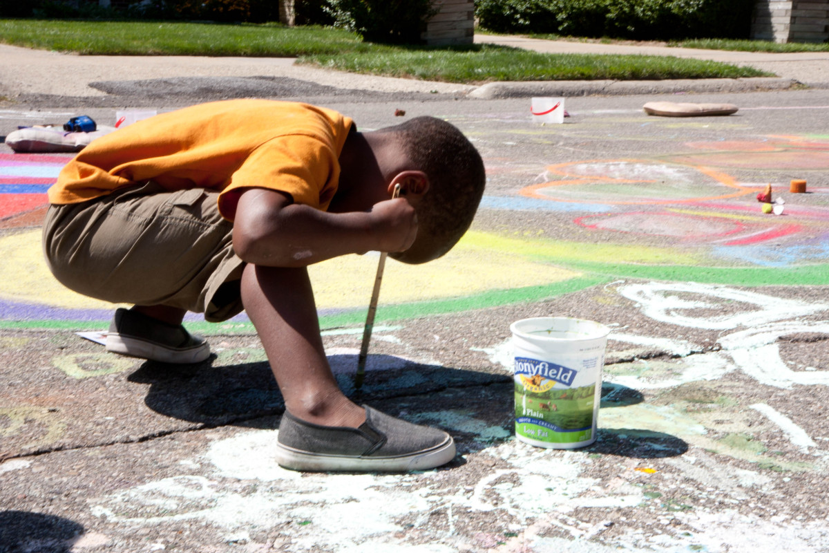 Kids play with chalk at an event supporting the creation of the world's longest hopscotch course in Detroit.