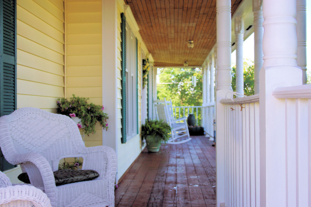 """White wicker chairs brighten up this rustic porch.  Photo by Flickr user <a href=""""http://www.flickr.com/photos/douggarner/3"""