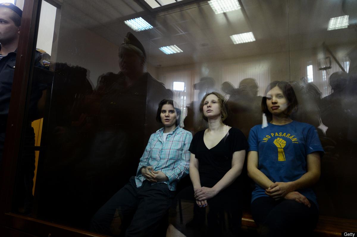 Members of the all-girl punk band 'Pussy Riot' Nadezhda Tolokonnikova, Maria Alyokhina and Yekaterina Samutsevich sit in a gl