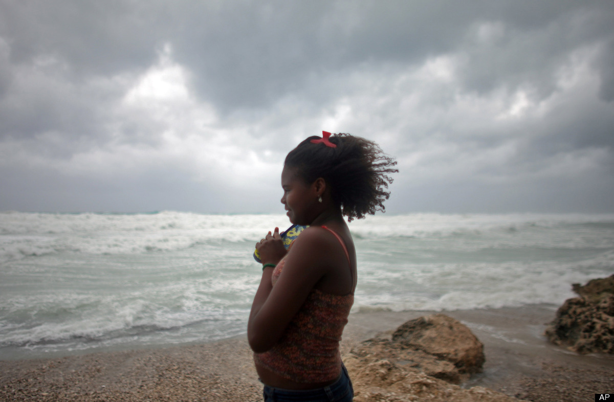 A woman looks out at the sea as Tropical Storm Isaac approaches Barahona, Dominican Republic, Friday, Aug. 24, 2012. Tropical