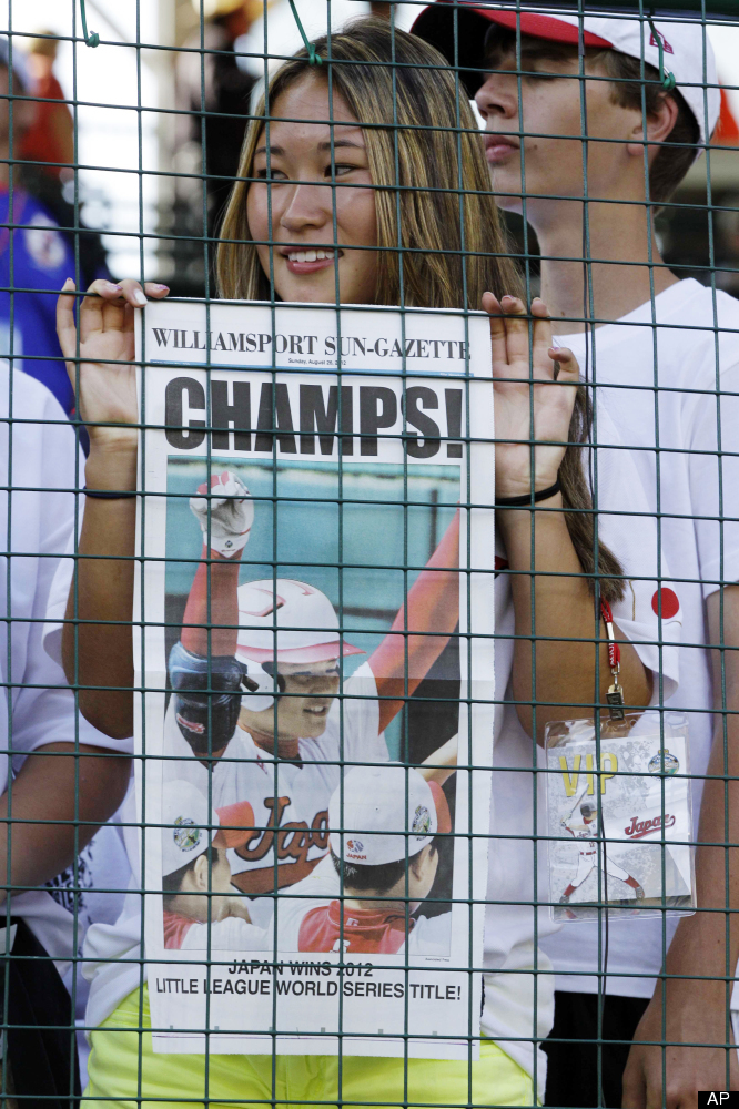 A fan of the Tokyo, Japan team holds a special edition of the front page of the Williamsport Sun-Gazette proclaiming Tokyo th