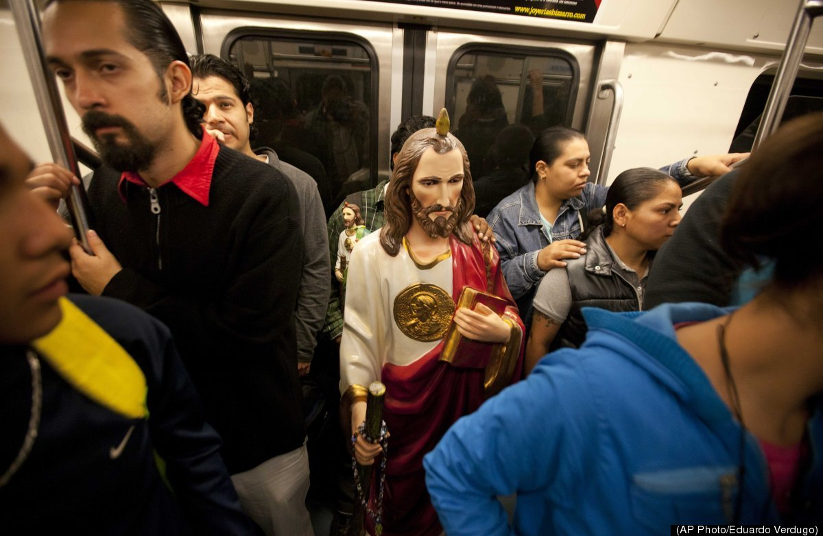 A large statue of Saint Jude, the Catholic saint of lost causes, stands in the metro surrounded by commuters in Mexico City,