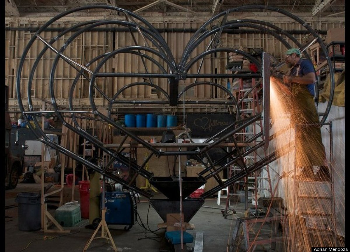 At right, Oakland resident Ric Boelkins sends sparks flying as assists metal sculptor Katy Boynton of San Francisco construct