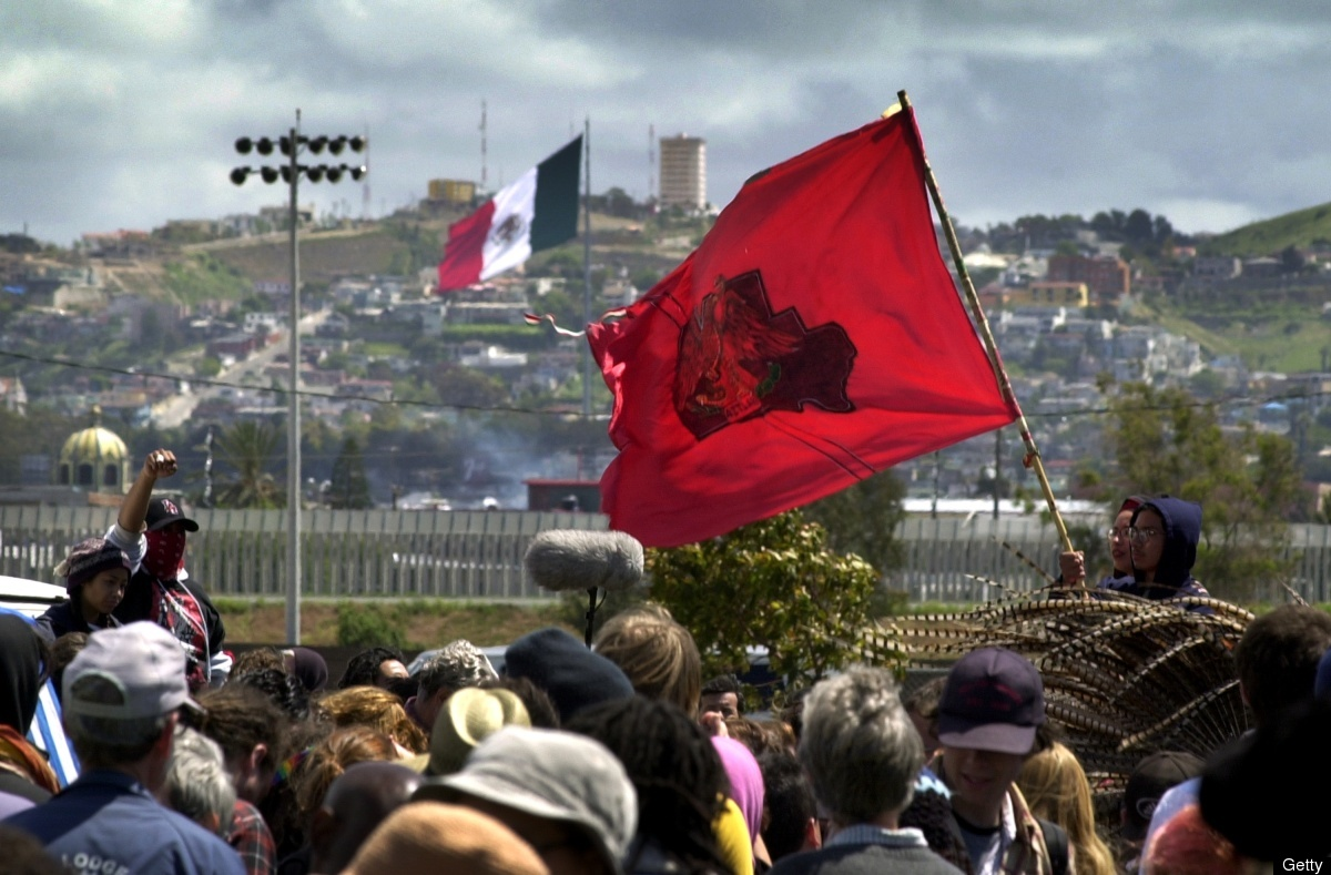 Protesters hold up a Chicano activist flag against a backdrop of the US/Mexico border fence behind which is Tijuana, Mexico a