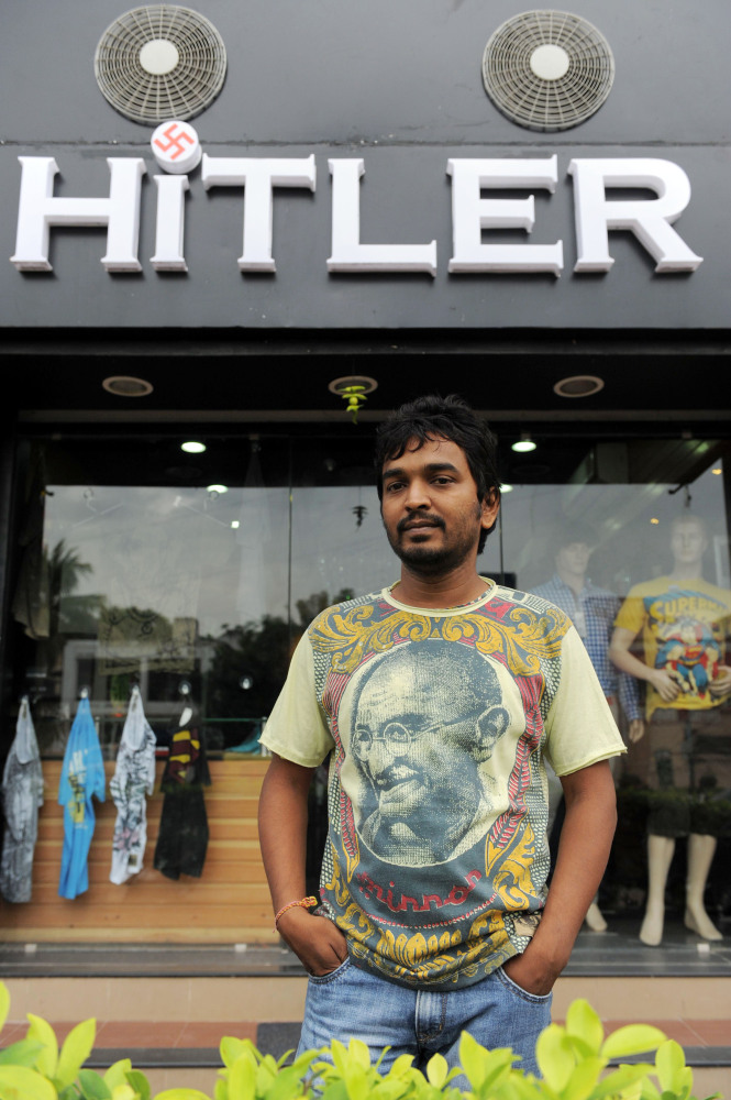 One of the two Indian owners of the 'Hitler' clothing store - Rajesh Shah  - poses in a T-shirt adorned with an image of Indi