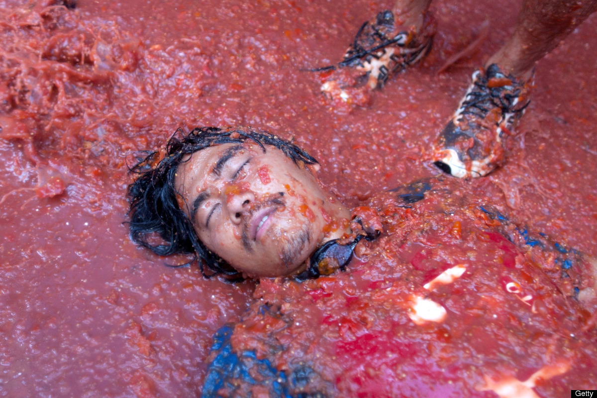 A reveler lays on tomato pulp while participating in the annual Tomatina festival on August 29, 2012, in Bunol, Spain. An est