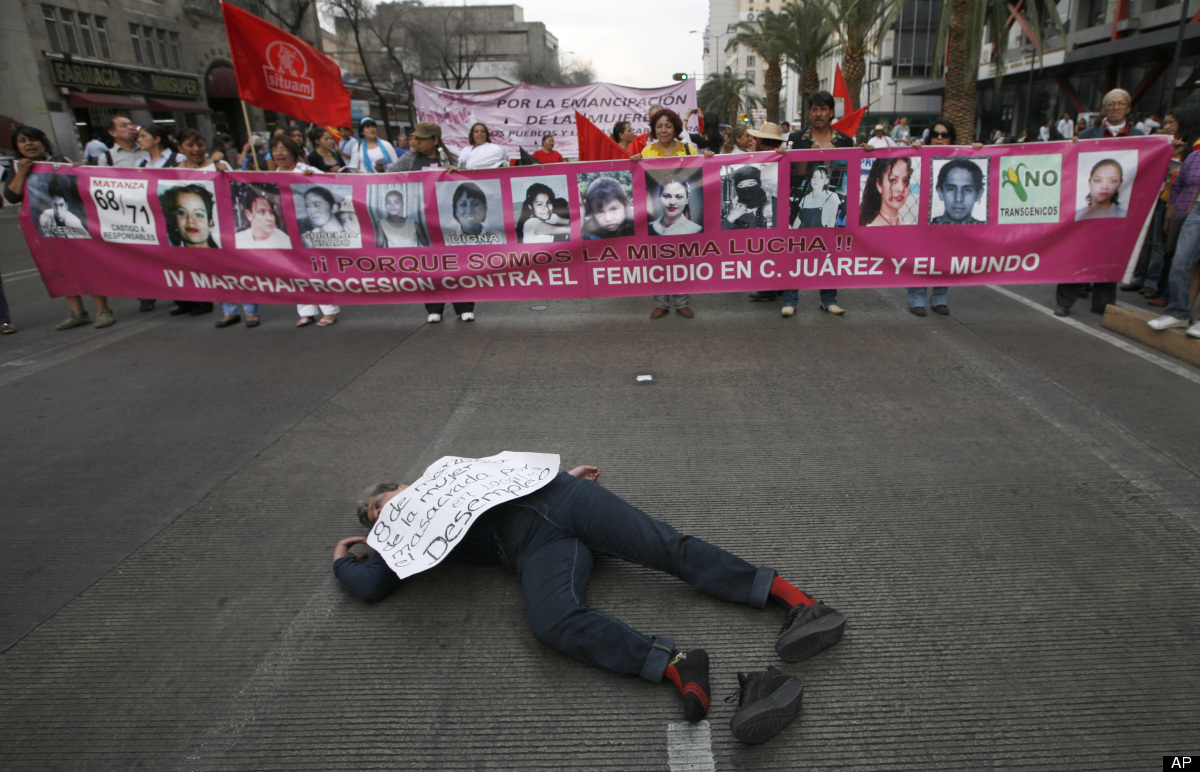Carrying images of women killed in the border city of Ciudad Juarez, demonstrators march as a woman lies on the ground during