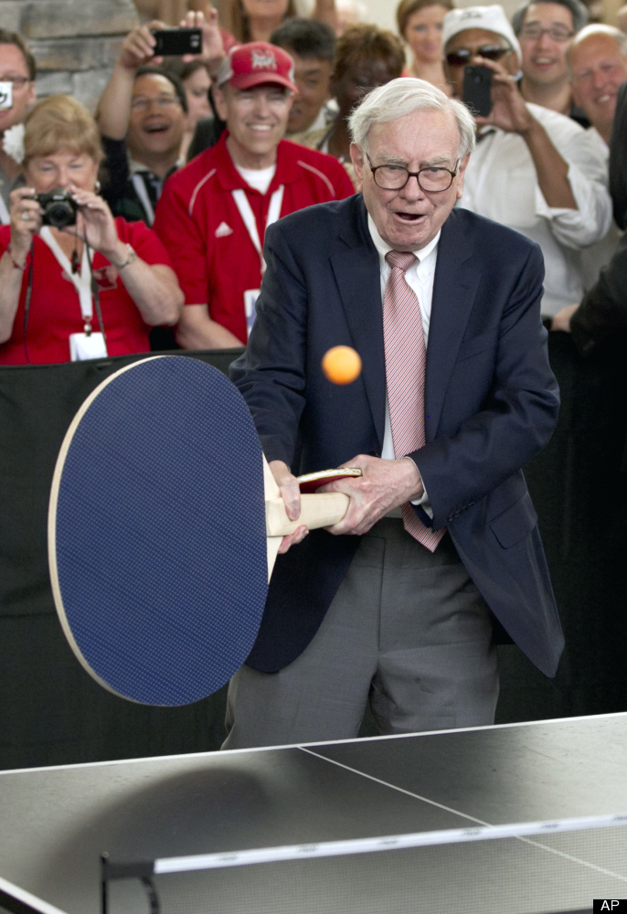 Here you see Warren Buffett using a giant paddle to hit an incredibly small ball.