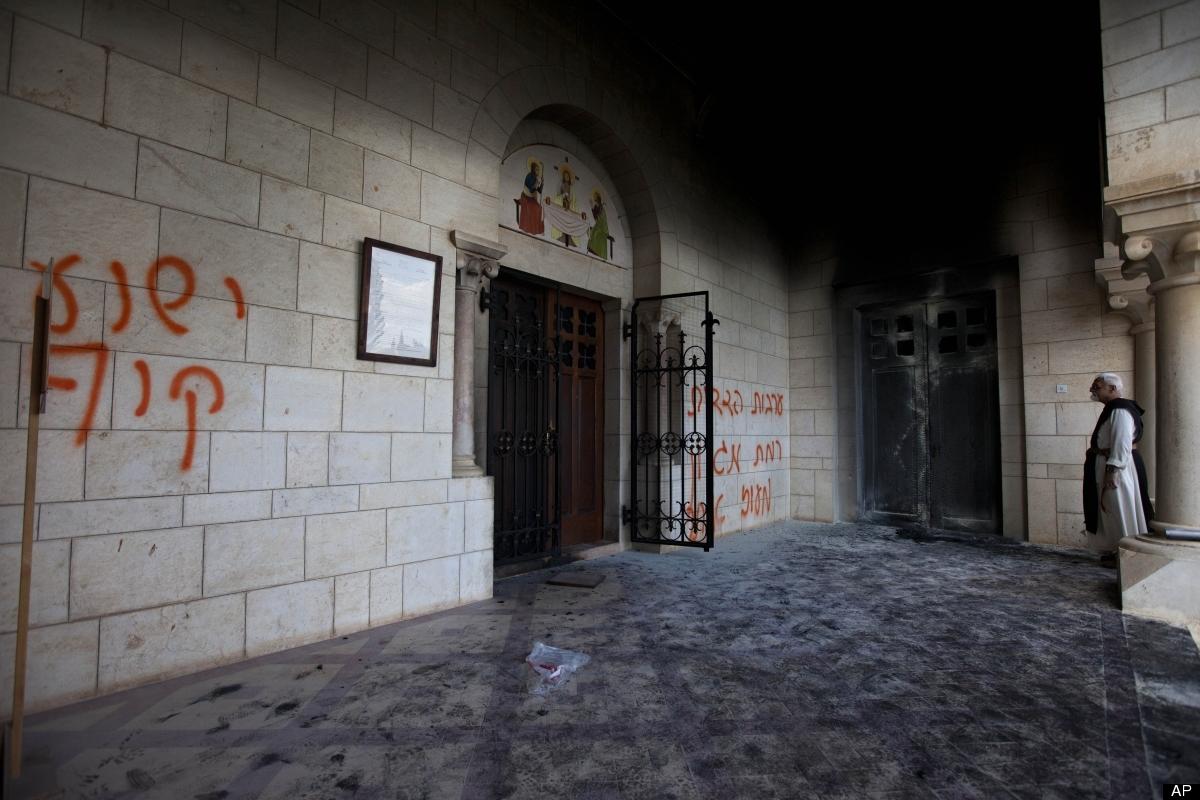 A catholic priest looks at anti-Christian graffiti written in Hebrew at the Latrun Trappist Monastery where Israeli police sa
