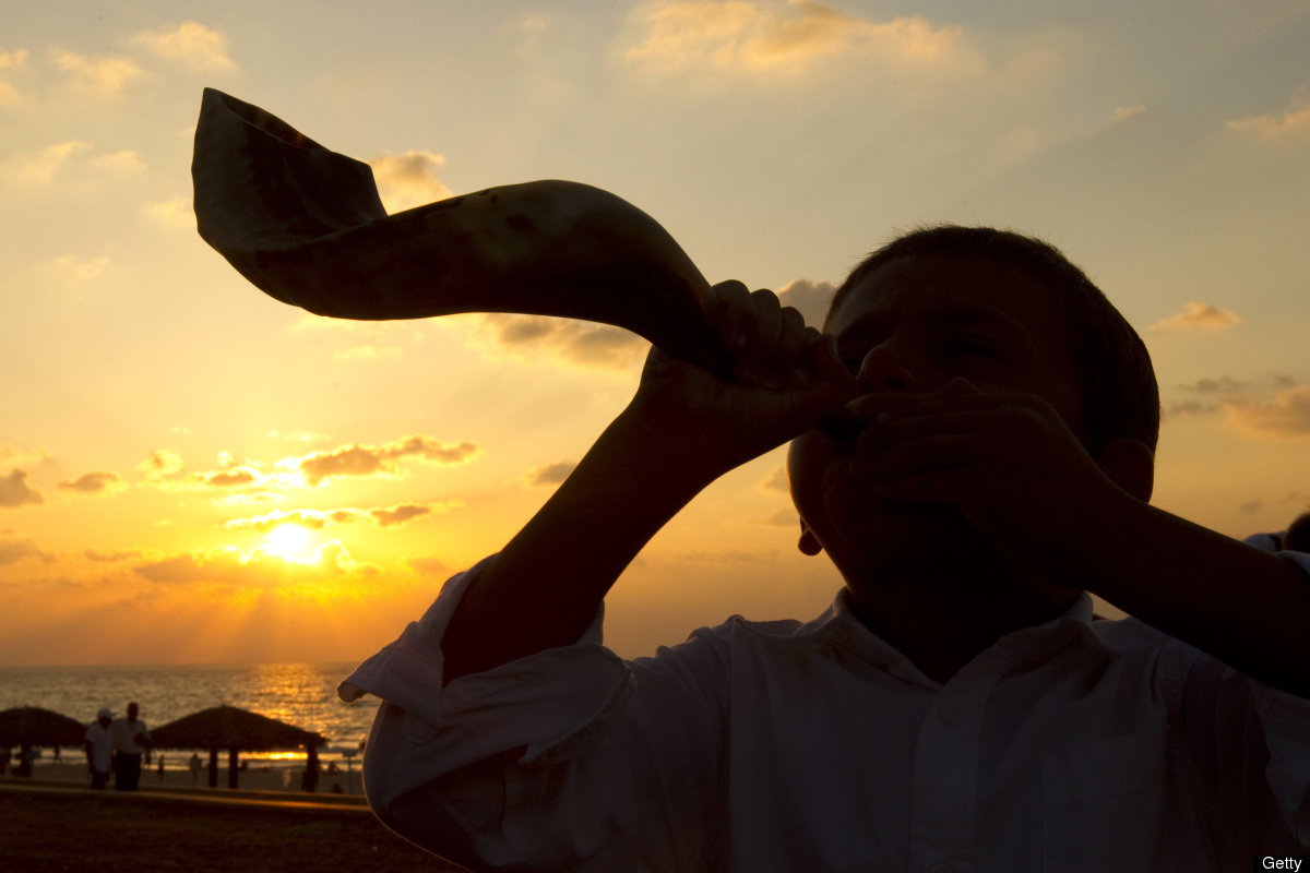 A young Jewish boy blows the shofar horn along the beach in the coastal city of Ashdod, during the ritual of Tashlich on Sept