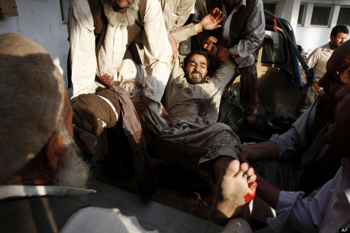 An injured Afghan man is carried into a hospital after a suicide attack on a funeral in the Durbaba district of Jalalabad, ea