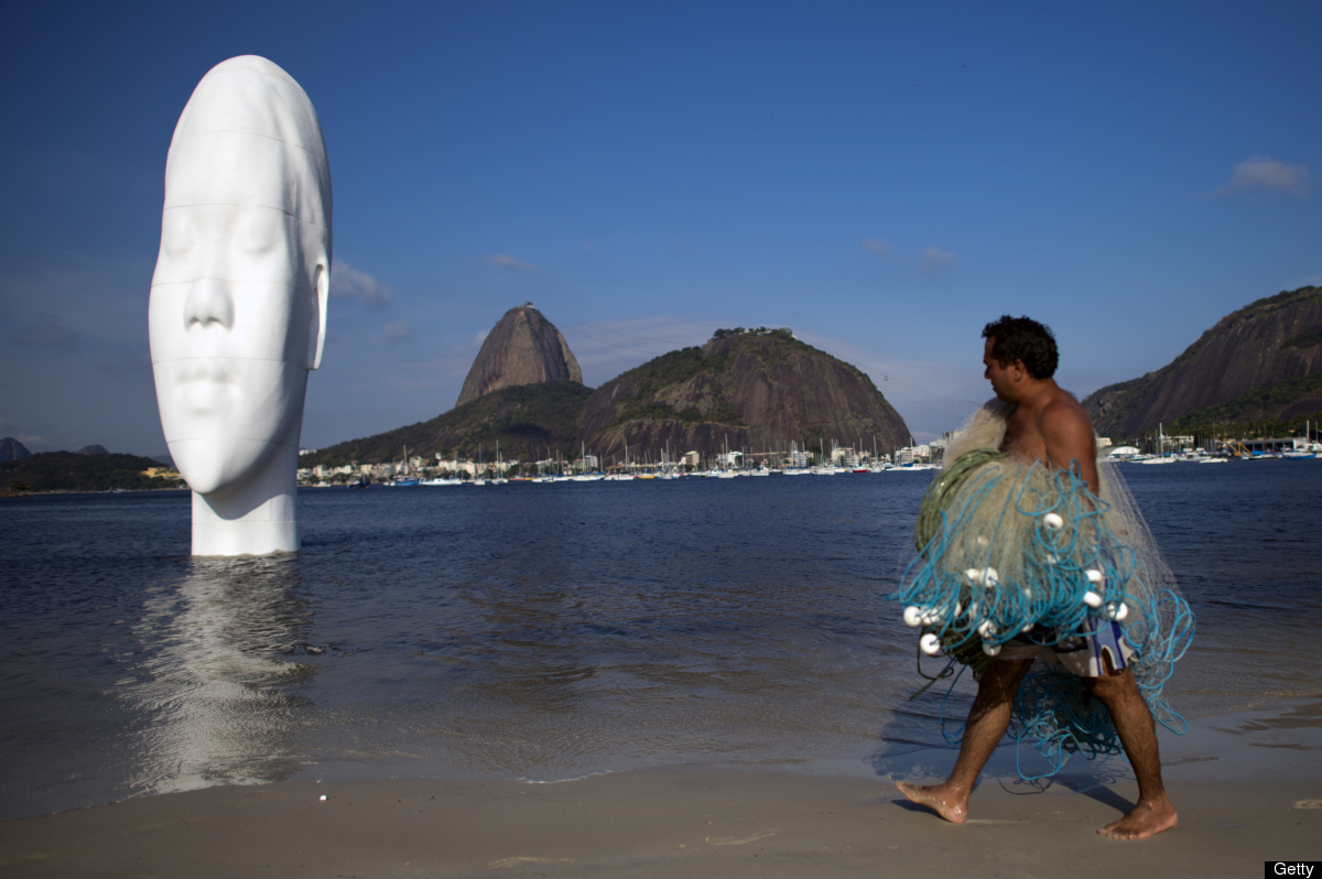 A fisherman looks at a huge sculpture by Spanish artist Jaume Plensa in Botafogo beach, in Rio de Janeiro, on September 3, 20