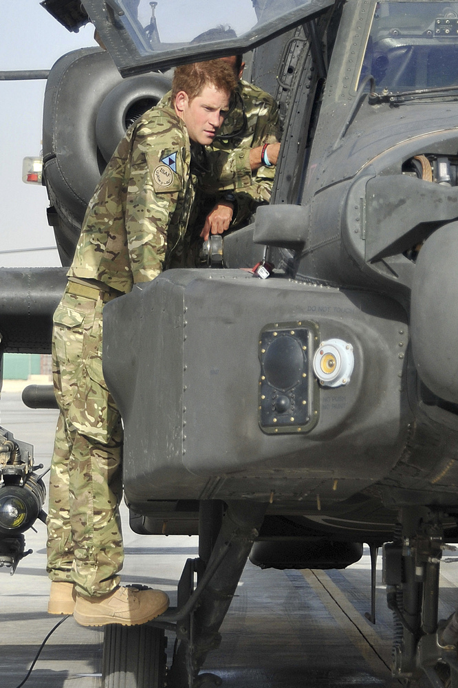 Britain's Prince Harry is shown an Apache helicopter by a member of his squadron, obscured behind, (name not provided) at Cam