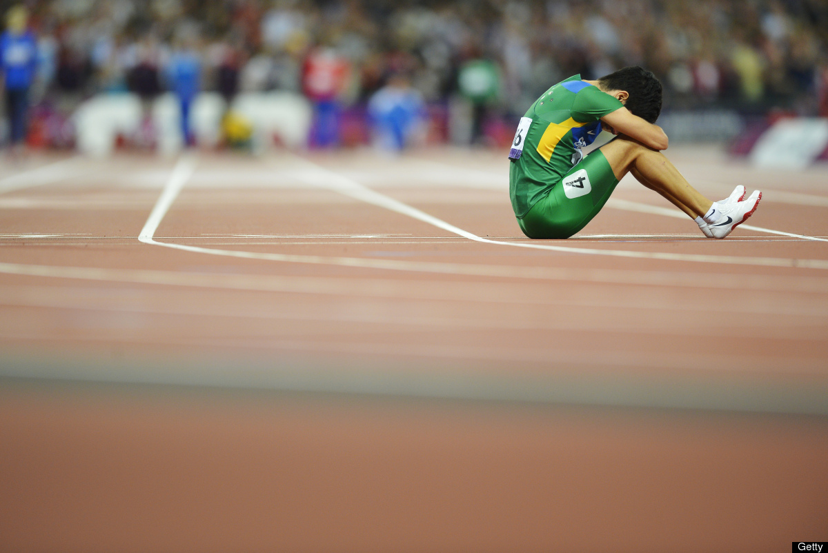 Brazil's Yohansson Nascimento sits on the finish line after falling and finishing last in the men's 100m T46 final during the