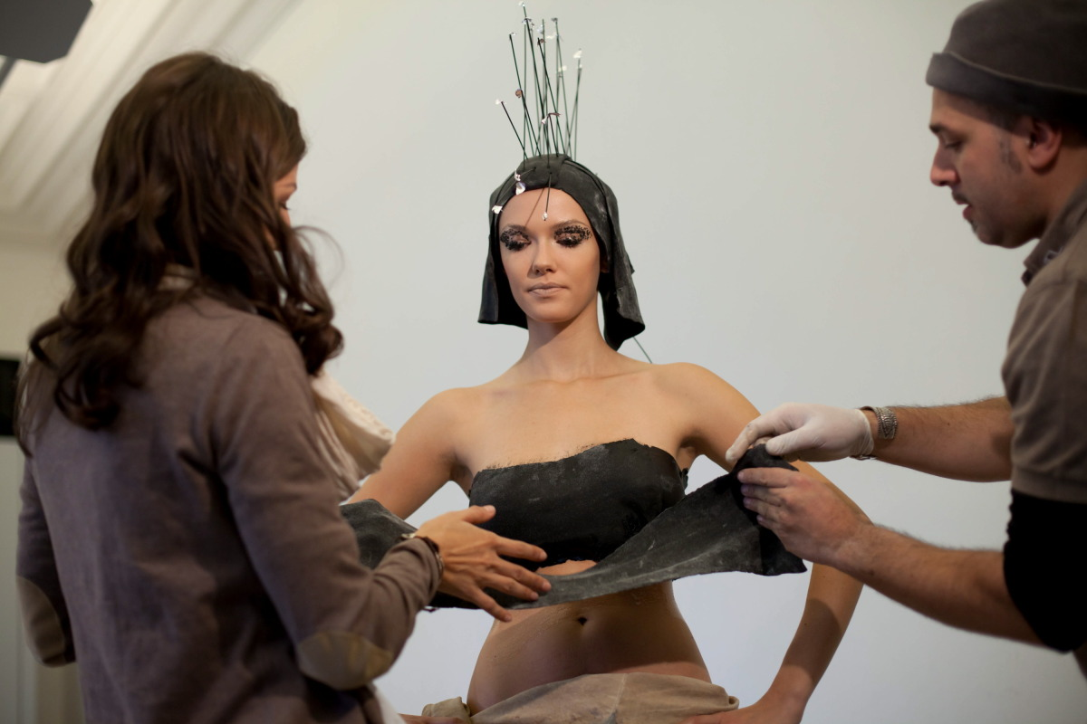 Trettl and the makeup artist are fitting Anna with a dough-based outfit.