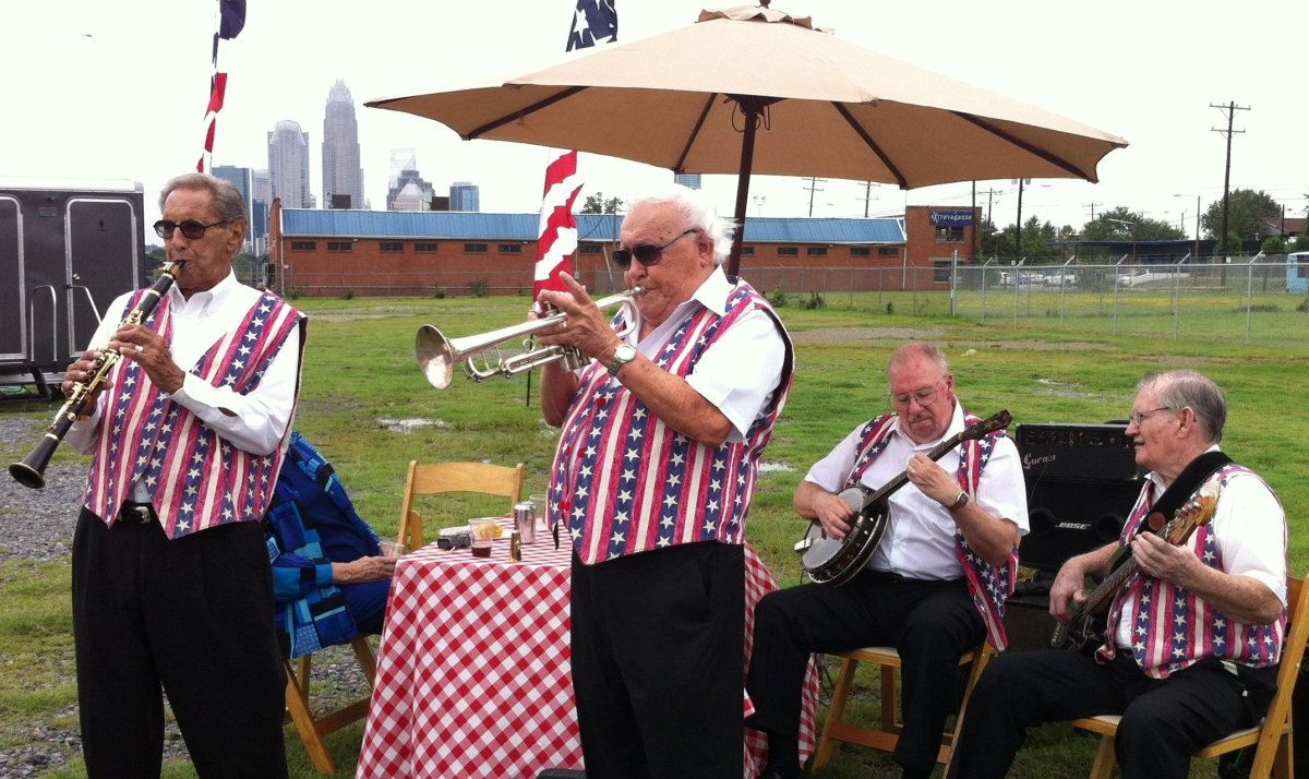 A ragtime band plays in front of the Charlotte skyline.  Behind them, the fabricating company for the DNC's huge banners, bun