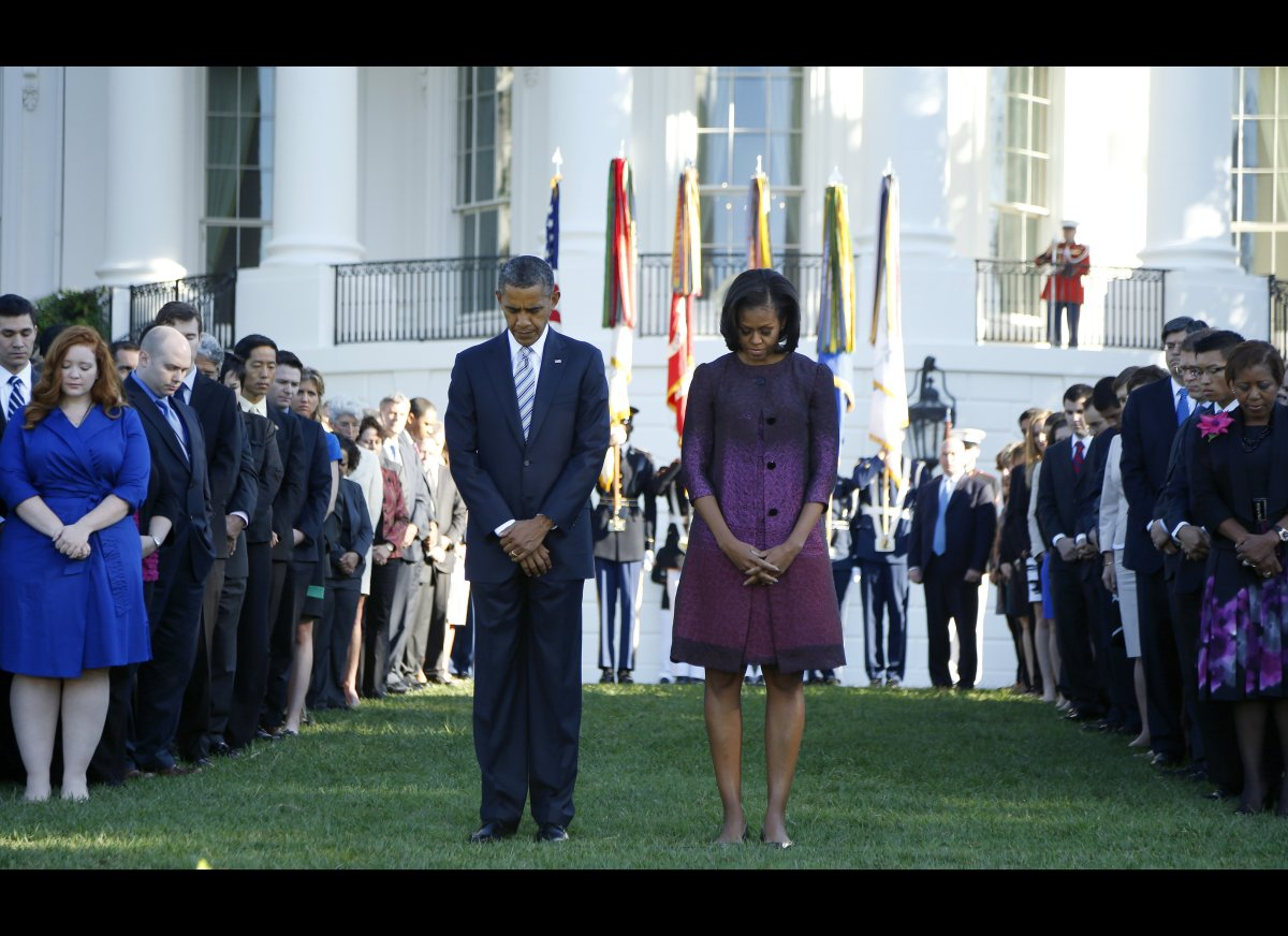 President Barack Obama, First Lady Michelle Obama, and members of the White House staff pause during a moment of silence to m