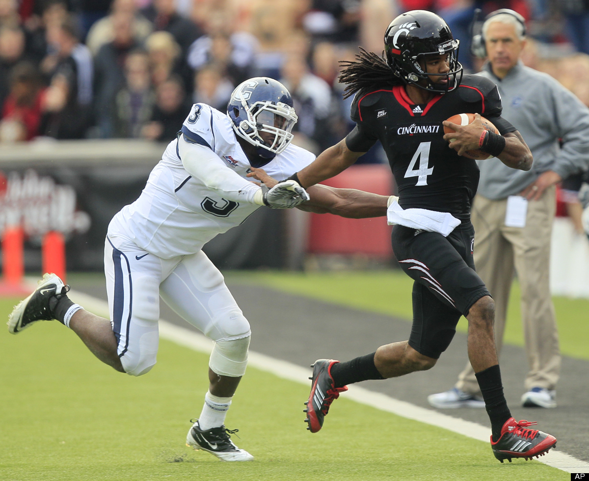 Cincinnati quarterback Munchie Legaux (4) is pushed out-of-bounds by Connecticut linebacker Sio Moore (3) in the first half o