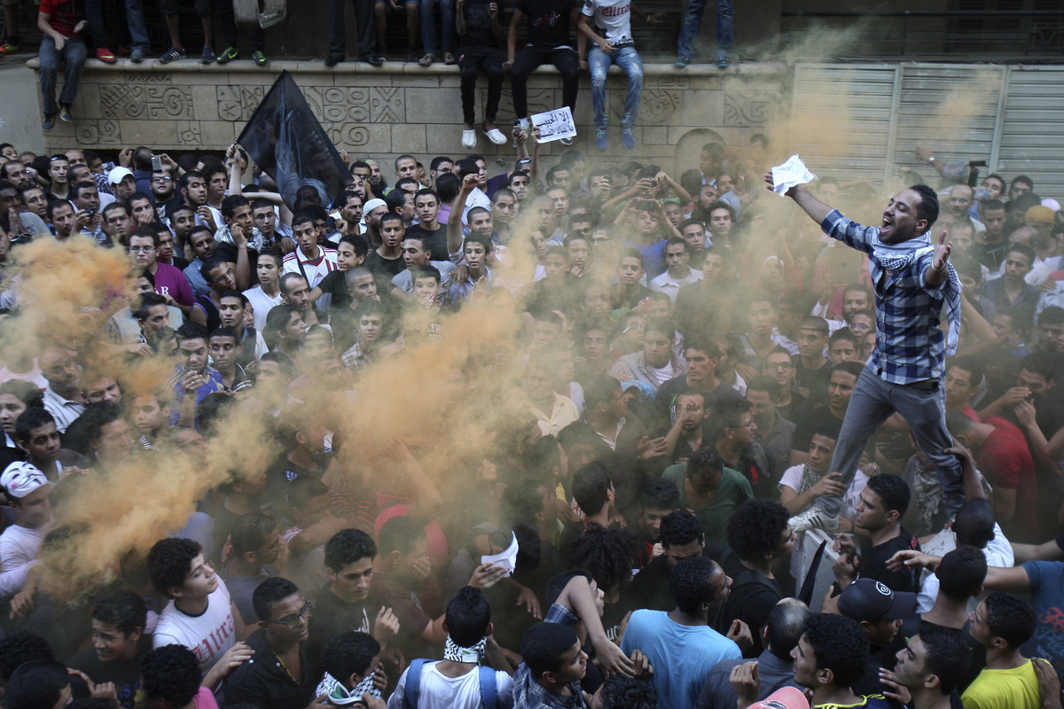 Protesters chant slogans amid orange smoke outside the U.S. embassy in Cairo, Egypt, Tuesday, Sept. 11, 2012. Egyptian protes